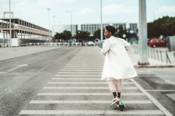 True tilt-shift shot of a young African female in glasses and a white fluttering cloak riding an e-scooter on a wide road with marking on it on a cloudy day