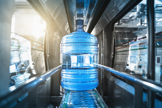 Plastic bottle or gallon of purified drinking water inside automated conveyor production line. Water factory