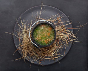 Soup with vegetables in a bowler hat, over hay. Countrylike shot top view