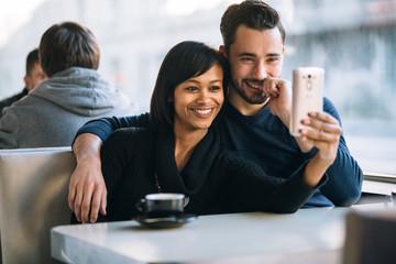 Interracial couple taking a selfie in coffee shop