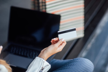 Fast shopping online. Close up photo, credit card and laptop computer to perform shopping online by inputting card.