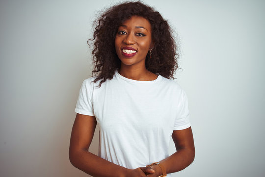 Young african american woman wearing t-shirt standing over isolated white background with hands together and crossed fingers smiling relaxed and cheerful. Success and optimistic
