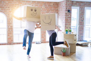 Couple wearing funny cardboard boxes with happy faces, moving to a new house, crazy and creative concept