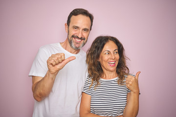 Beautiful middle age couple together standing over isolated pink background smiling with happy face...
