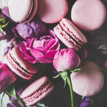 Sweet pink macaron cookies and spring rose flowers, buds and petals over wooden background, top view, selective focus, close-up, square crop. Food texture, background and wallpaper
