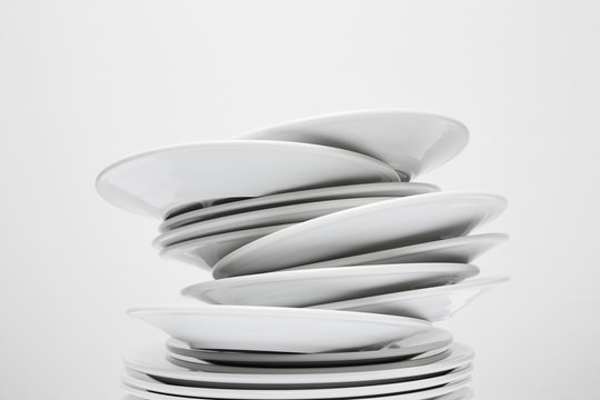 Messy stack of white plates about to fall, isolated on white