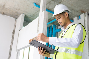 inspector open and checking infomation paper of construction materials in building