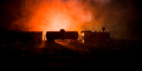Train moving in fog. Ancient steam locomotive in night. Night train moving on railroad. orange fire background.