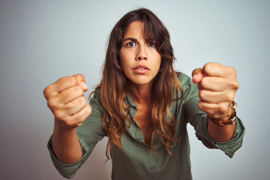 Young beautiful woman wearing green shirt standing over grey isolated background angry and mad raising fists frustrated and furious while shouting with anger. Rage and aggressive concept.