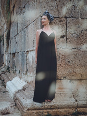 Close-up view of beautiful young, attractive Muslim woman in long black dress standing on the corner of Hidirlik tower