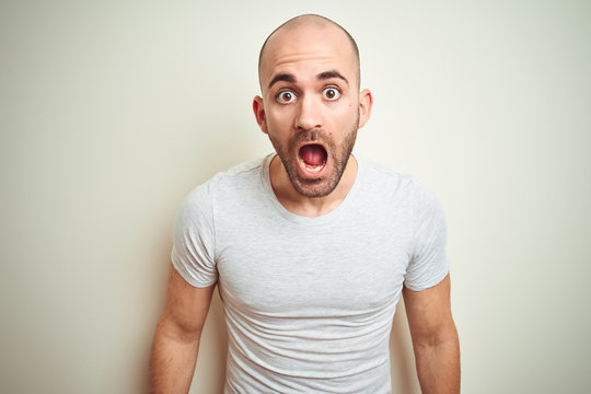 Young bald man with beard wearing casual white t-shirt over isolated background afraid and shocked with surprise expression, fear and excited face.