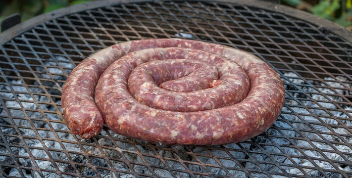 South African boerewors sausage traditionally cooked outdoors on an open fire image with copy space in horizontal format