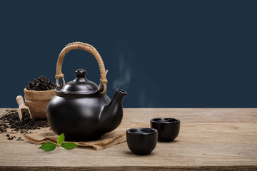 Photo sur Aluminium The Cup of hot tea with teapot, green tea leaves and dried herbs on the wooden table isolate dark blue background with empty space, Organic product from the nature for healthy with traditional