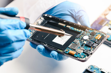 The technician repairing the smartphone's motherboard in the lab by soldering method. the concept of computer hardware, mobile phone, electronic, repairing, upgrade and technology.
