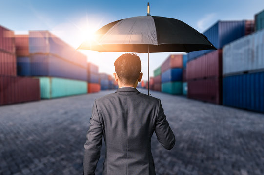 The abstract image of the Businessman is spreading umbrella during sunrise overlay with container yard image. The concept of transportations, business, insurance, and protection.