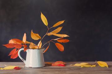 Fototapeta autumn leaves in jug on wooden table on dark background obraz
