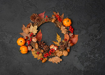 autumn Thanksgiving wreath with pumpkin, fall leaves, red berries, acorns on dark background. autumn holiday, fall, thanksgiving, halloween concept. Flat lay, top view, copy space