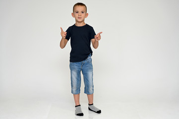 Full-length portrait on a white background of a cute boy child with Vitiligo disease - a violation of the color of the skin at the initial stage. Black T-shirt, blue jeans.