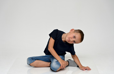 A full-length portrait of a cute boy child sitting on the floor on a white background with Vitiligo disease is a violation of the color of the skin at the initial stage. Black T-shirt, blue jeans.