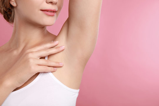 Young woman with smooth clean armpit on pink background, space for text. Using deodorant