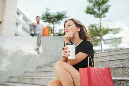Smiling dreamy beautiful young woman sitting outdoors on steps and enjoying cup of coffee after shooping