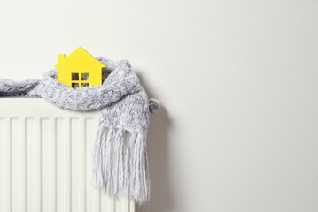 House model wrapped in scarf on radiator indoors, space for text. Winter heating efficiency Wall mural