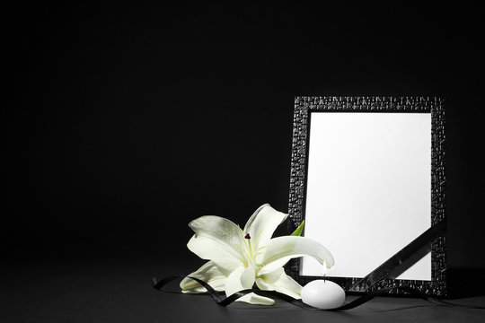 Funeral photo frame with ribbon, white lily and candle on black background. Space for design