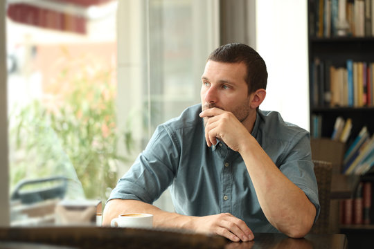 Pensive man in a coffee shop looking through a window
