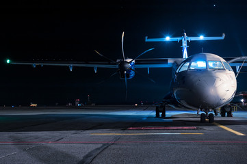 The plane stands at the airport at night