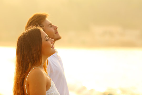 Relaxed couple on the beach breathing fresh air at sunset