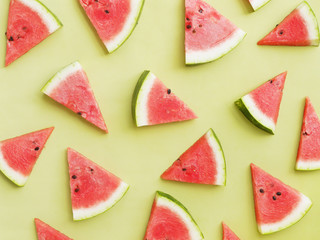 Fototapete - Watermelon slices on a green background pattern, top view, flat layout.