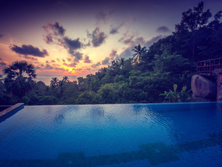 Fototapete - Infinity beach pool, sunset sky horizon and colorful clouds. Luxury vacation and holiday concept, outdoor scenic