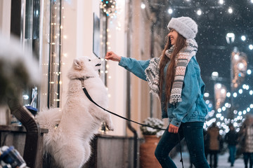 Photo of a young woman and a white dog who shows tricks on an street