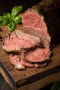 Juicy roast beef with spices sliced on a cutting Board, delicious meat, traditional food. On dark background