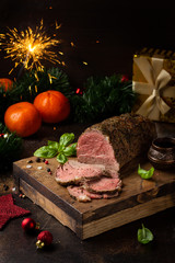 Juicy roast beef with spices sliced on cutting Board, delicious meat, traditional food. Christmas holidays, new year, menu on dark background
