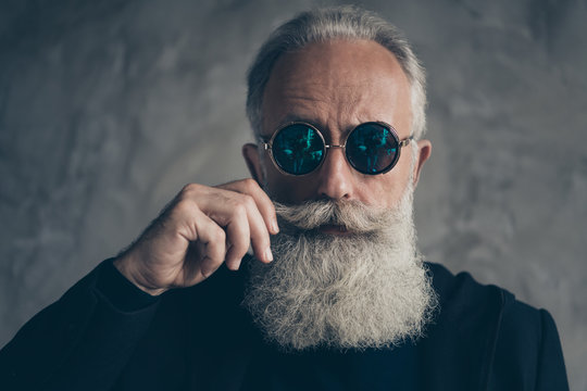 Close up photo of attractive harsh masculine pensioner in eyewear eyeglasses touching his moustache isolated over grey background