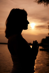 Silhouette of woman standing in praying position at sunset. Yoga exercising concept.