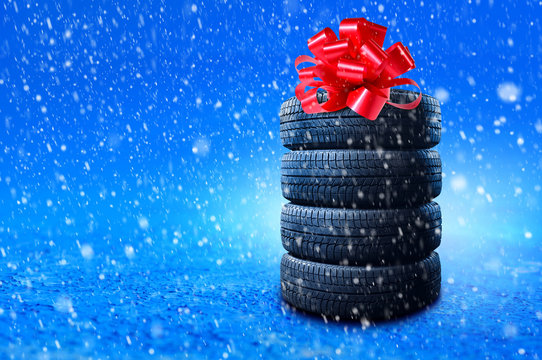 New winter tires pile as a gift. Tyres pile with a big red bow, as a present or bonus for buying a car. Banner with copy space.