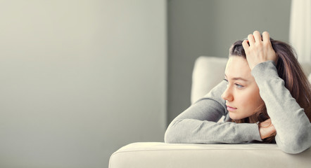 Depressed young woman on sofa at home.
