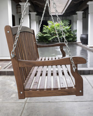 The detail of brown wood swing in the backyard.