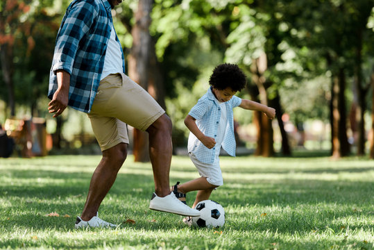 cropped view of african american father playing football with son