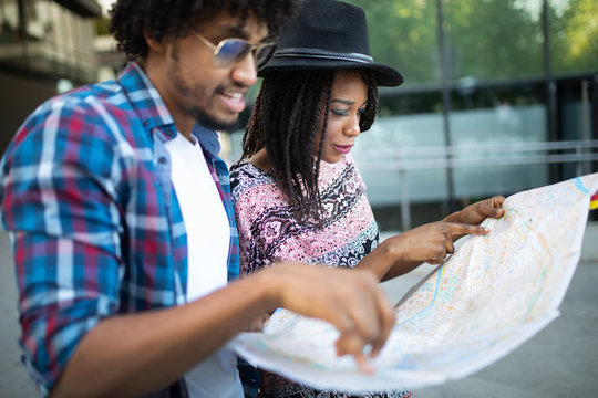 Summer holidays, dating and tourism concept. Smiling couple with map in the city