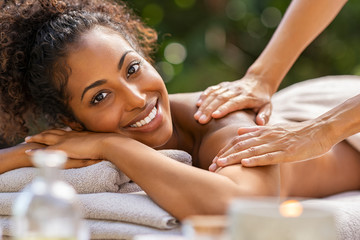 Black woman relaxing during spa massage