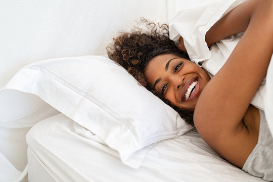 African beautiful girl playing with blanket on bed