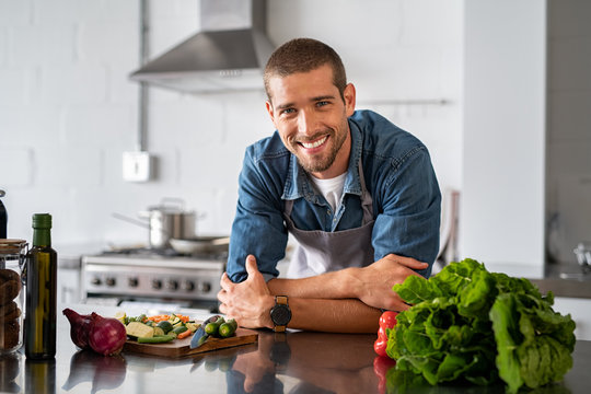 Happy man ready to cook in kitchen