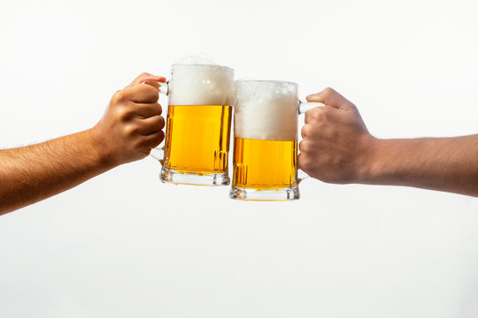 Hands toasting with beer on white background