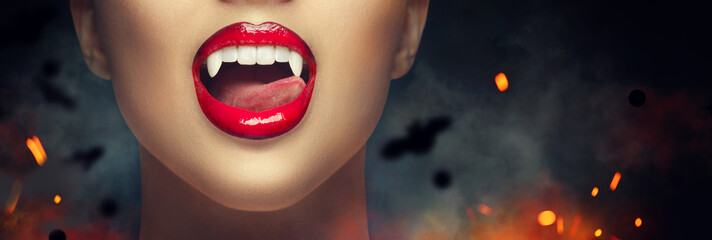 Sexy Vampire Woman's red bloody lips close-up. Vampire girl licking fangs with tongue. Fashion Glamour Halloween art design. Close up of female vampire mouth, teeth. Vampire woman teeth closeup