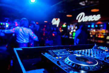 control DJ for mixing music with blurred people dancing at party in nightclub