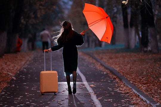 night the girl is walking with an umbrella and a suitcase in the autumn park, the concept of travel, sadness, parting, divorce