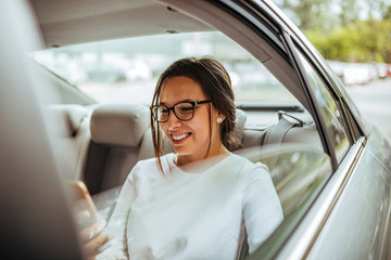Portrait of a beautiful smiling woman sitting on the backseat of a taxi being driven to the office.